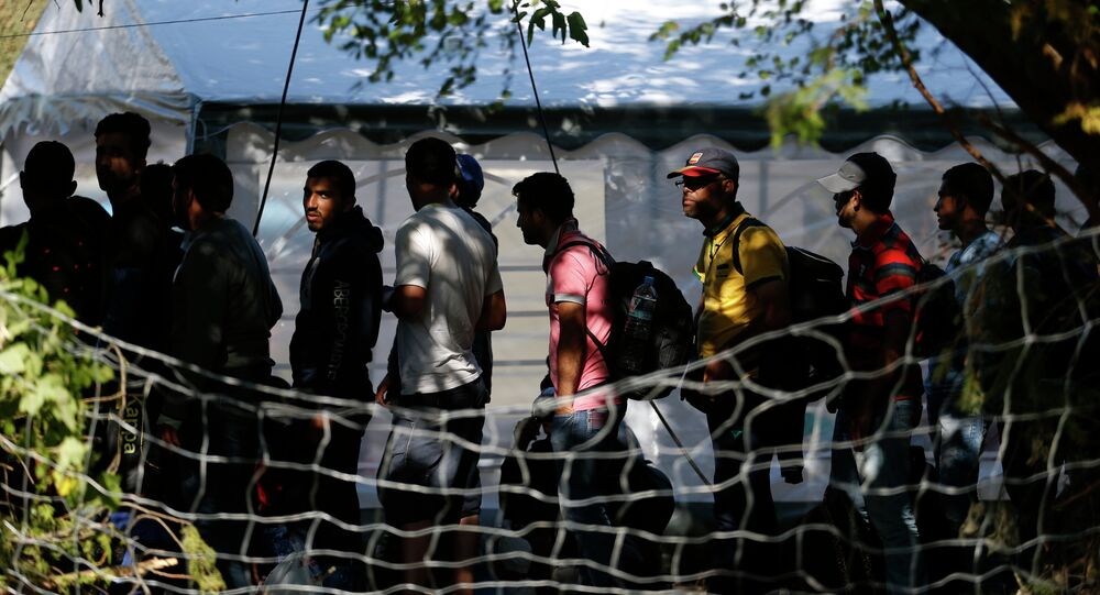Migrants wait to register with the police at a migrant processing center in the southern Serbian town of Presevo, Monday, Aug. 24, 2015