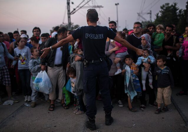 A Greek police officer gives orders to Syrian refugees as they wait to cross the border from Greece to Macedonia, in the border town of Idomeni , northern Greece, on Wednesday, Aug. 26, 2015