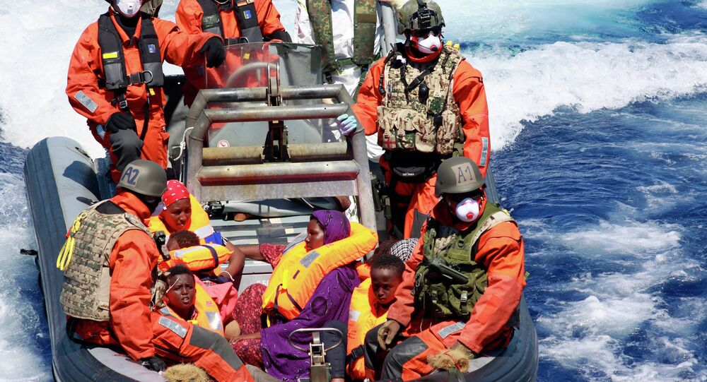 In this Aug. 23, 2015 picture provided by the German Navy pregnant Somali refugee, Rahma Abukar Ali center, sits in a boat of the German Navy in the Mediterranean Sea, near Italy