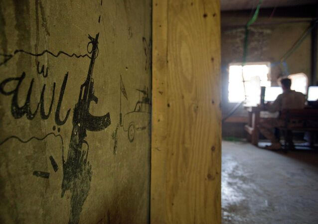 Taliban graffiti shows an AK-47 assault rifle and the word 'Allah' at left, translated from Pashto, decorating a wall in the Musa Qala district center.