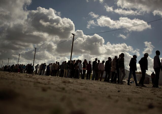 Migrants line up as the wait for a food ration distributed by the Banque Alimentaire of Calais at a camp in northern France, Tuesday, Aug. 4, 2015