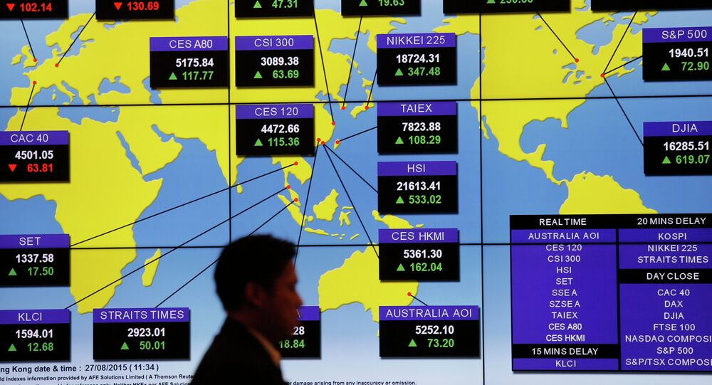 A man walks past a bank's electronic board showing the share index around the world at Hong Kong Stock Exchange Thursday, Aug. 27, 2015