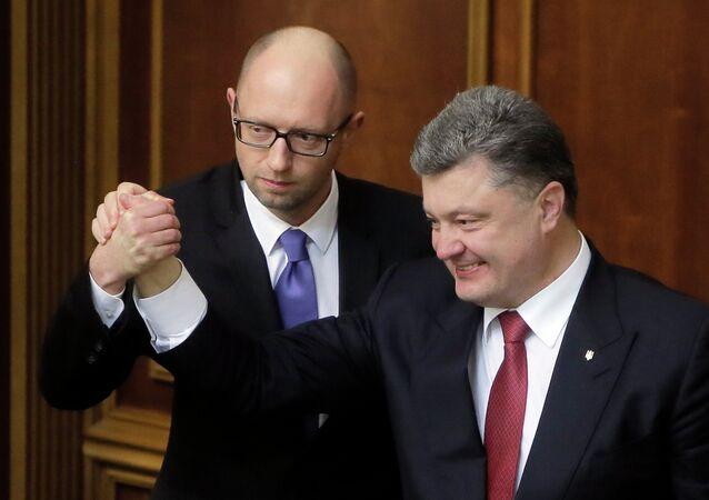 Ukraine's President Petro Poroshenko, right, and Prime Minister Arseniy Yatsenyuk celebrate after Yatsenyuk was appointed the Prime Minister during the opening first session of the Ukrainian parliament in Kiev, Ukraine