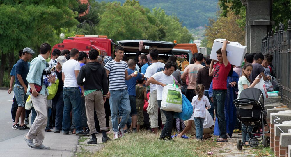 Refugees are trying to salvage some free stuff donated by an unknown donor outside of Austria's main refugee processing centre in Traiskirchen on July 31, 2015