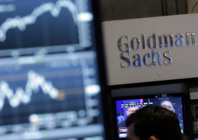 A screen at a trading post on the floor of the New York Stock Exchange is juxtaposed with the Goldman Sachs booth