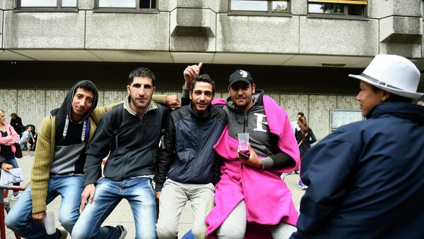 Syrian refugees queue outside outside the State Office of Health and Social Affairs in Berlin (LAGeSo) where hundreds of migrants wait to receive help from the Berlin administration on August 25, 2015 - Sputnik International