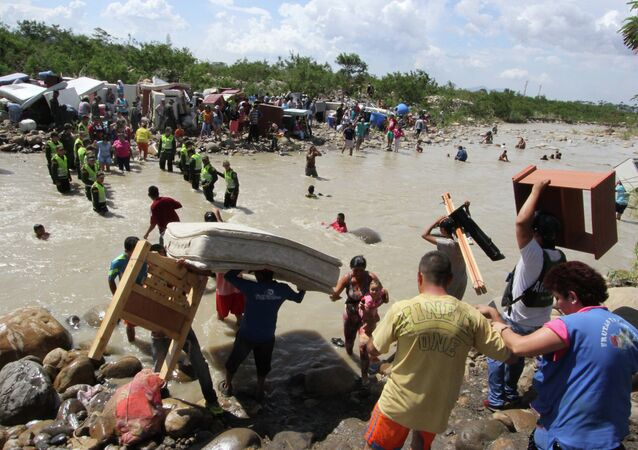 People carry their household belongings across the Tachira River from Venezuela, foreground, to Colombia, near San Antonio del Tachira, Venezuela, Tuesday, Aug. 25, 2015, during a mass exodus of Colombians living on the Venezuelan side of the border