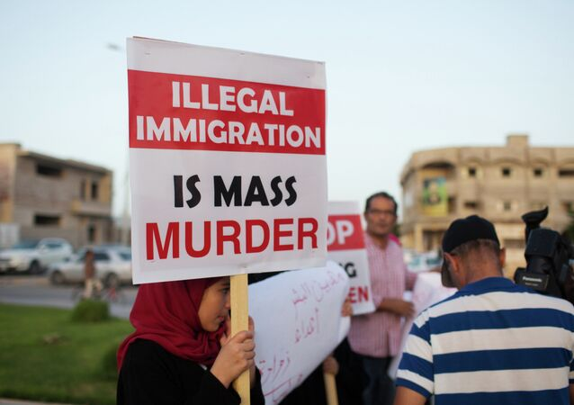 In this Thursday, Aug. 27, 2015 photo, local residents hold a demonstration against illegal immigration after hearing news that a boat carrying hundreds of migrants capsized off the coast, in Zuwara, Libya