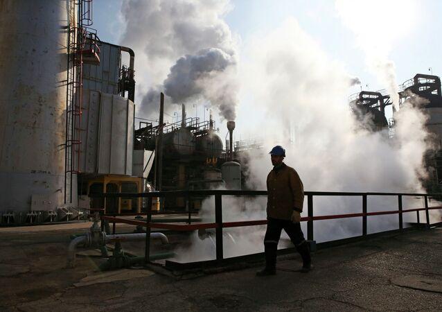 An Iranian oil worker walks in Tehran's oil refinery south of the capital Tehran, Iran, Monday, Dec. 22, 2014