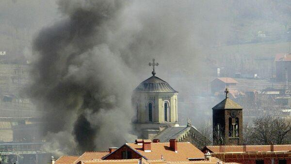 Smoke billows from Serbian Orthodox Church which was set ablaze by ethnic Albanian extremists in the northern Kosovo city of Kosovska Mitrovica, Thursday, March 18, 2004 - Sputnik International