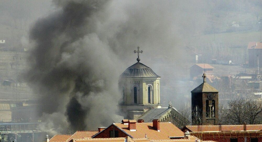 Smoke billows from Serbian Orthodox Church which was set ablaze by ethnic Albanian extremists in the northern Kosovo city of Kosovska Mitrovica, Thursday, March 18, 2004