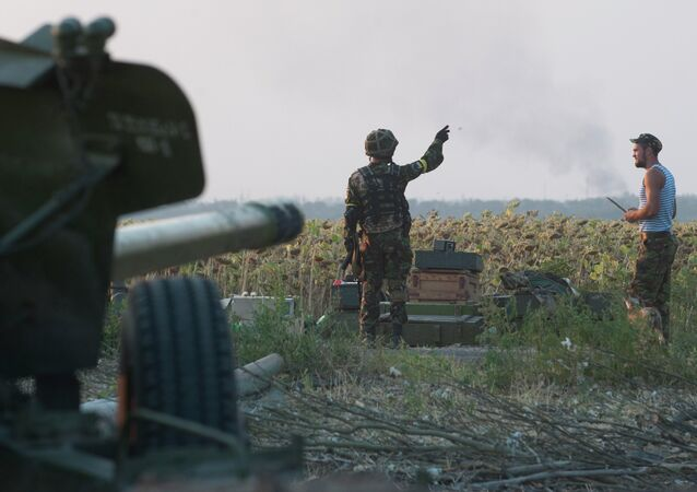 In this photo taken on Thursday, Aug. 14, 2014, a Ukrainian government soldier points on a smoke after shelling near Illovaisk, Donetsk region, eastern Ukraine