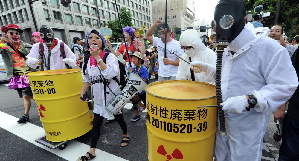 Protesters wearing gas masks and white costumes similar to those of decontamination workers at the crippled Fukushima plant beat drums painted with radioactive waste symbols during an anti nuclear power demonstration march in Tokyo.