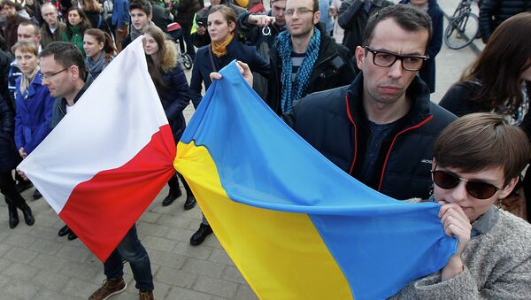 People holding a Poland flag, left, and a Ukraine flag listen to speakers during a demonstration in Warsaw, Poland showing their support for protesters in Ukraine - Sputnik International
