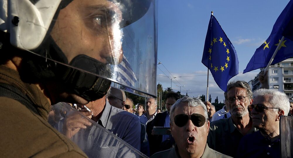 Riot police stand between anti-austerity and pro-EU protesters in front of the parliament building during a rally calling on the government to clinch a deal with its international creditors and secure Greece's future in the eurozone in Athens, Greece, in this June 22, 2015 file photo