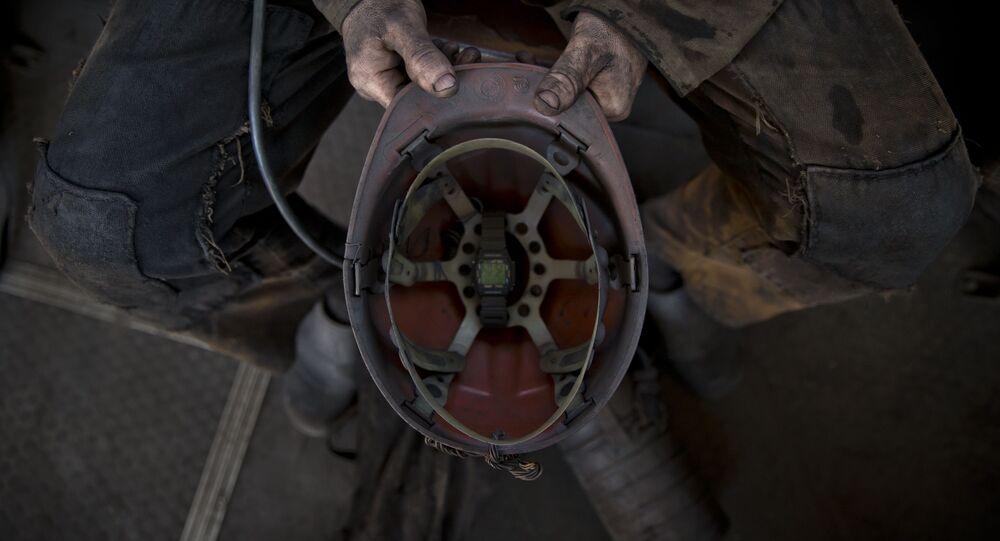 A Ukrainian coal miner holds his helmet after finishing his shift at a coal mine outside Donetsk, Ukraine