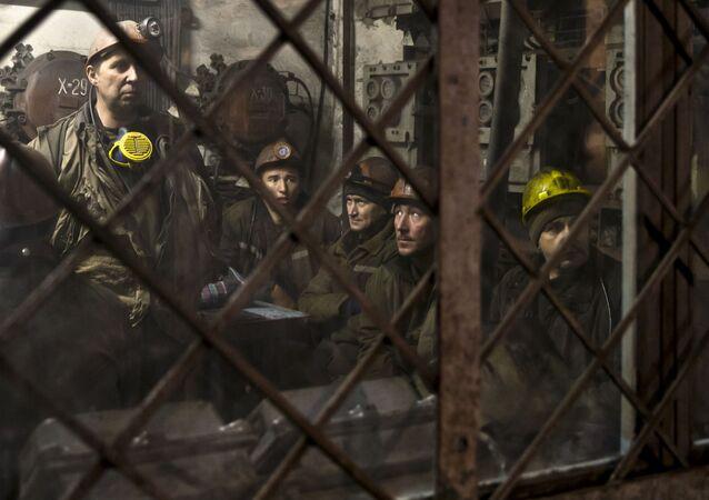 Ukrainian coal miners wait in a room before going underground at the Zasyadko mine in Donetsk, Ukraine
