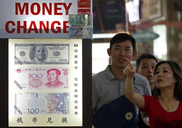 People look at the exchange rate at a moneychanger displaying a poster of US dollar bill, Chinese Yuan and Malaysia Ringgit