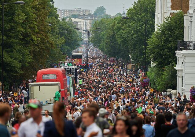 Visitors line the streets of Ladbrooke Grove as the carnical floats pass by on the first day of the Notting Hill Carnival in west London on August 30, 2015