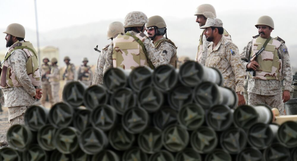 Saudi soldiers from an artillery unit stand behind a pile of ammunition.