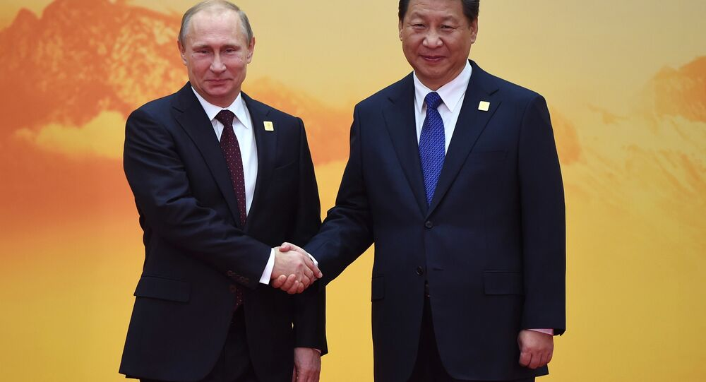 Russia's President Vladimir Putin (L) shakes hands with China's President Xi Jinping