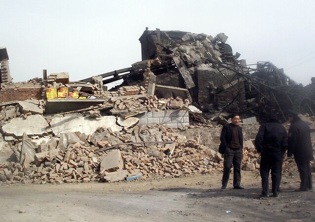 Police and officials stand beside debris from a collapsed mine.