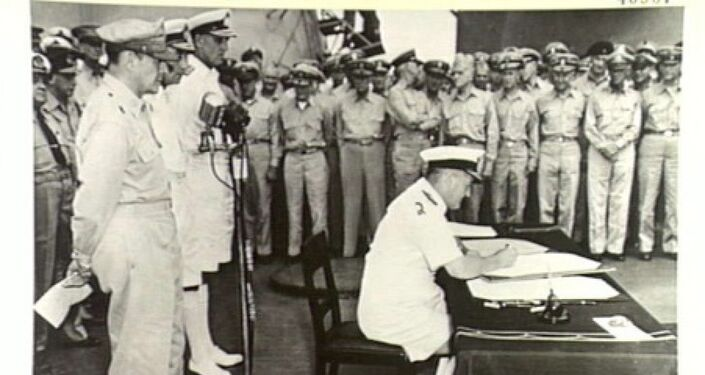 Admiral Sir Bruce Fraser, commanding British Pacific fleet, signs the instrument of surrender on behalf of the United Kingdom.