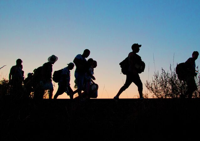 A group of refugees walk on the railway tracks after crossing from Serbia, into Roszke, Hungary, Tuesday, Sept. 1, 2015.