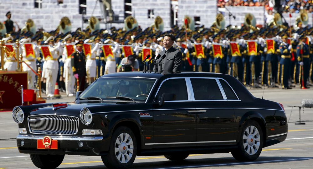 Chinese President Xi Jinping stands in a car on his way to review the army as military band members play next to him, at the beginning of the military parade marking the 70th anniversary of the end of World War Two, in Beijing, China, September 3, 2015
