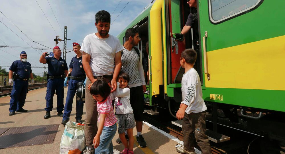 Migrants stand outside a train at the railway station in the town of Bicske, Hungary, September 3, 2015