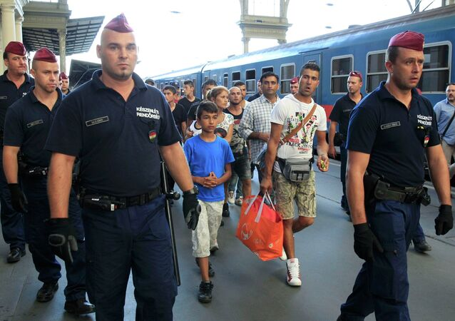 Hungarian police officers guard refugees to a regional train supposed to carry them to a nearby interim camp at a railways station in Budapest, Hungary September 2, 2015