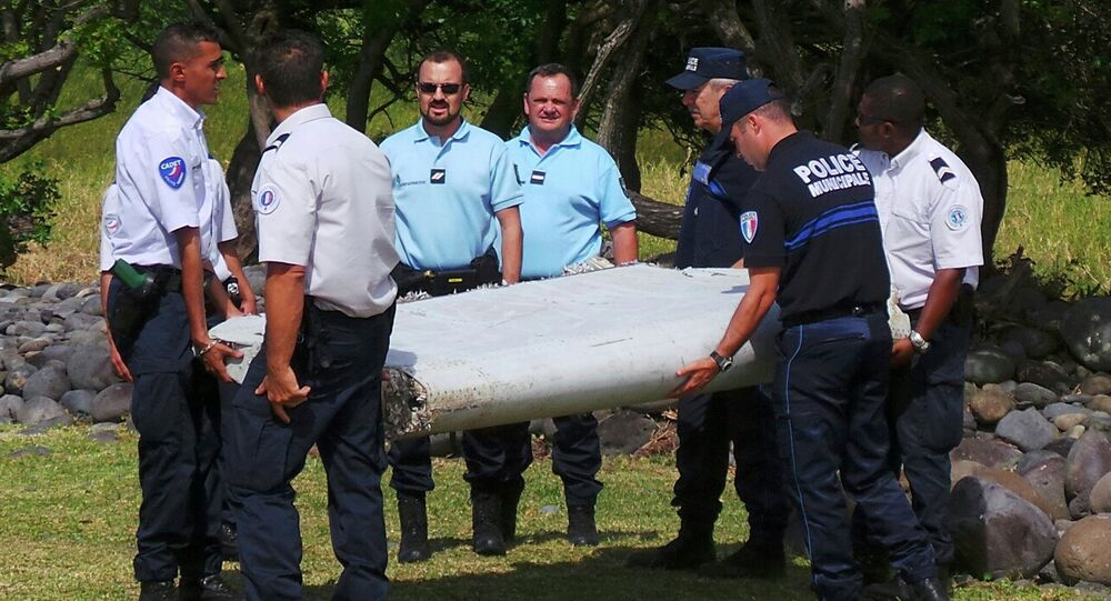 French gendarmes and police carry a large piece of plane debris which was found on the beach in Saint-Andre, on the French Indian Ocean island of La Reunion, in this picture taken July 29, 2015