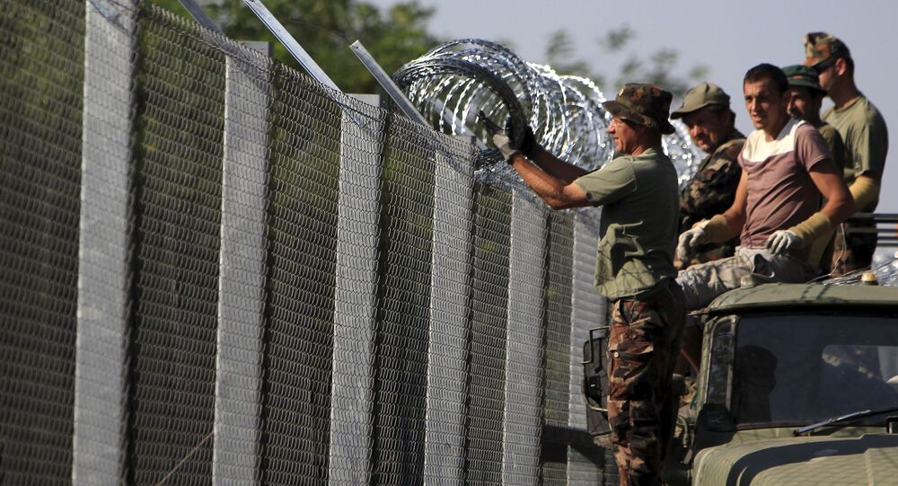 Hungarian soldiers adjust the razor wire on a fence near the town of Asotthalom, Hungary, August 30, 2015