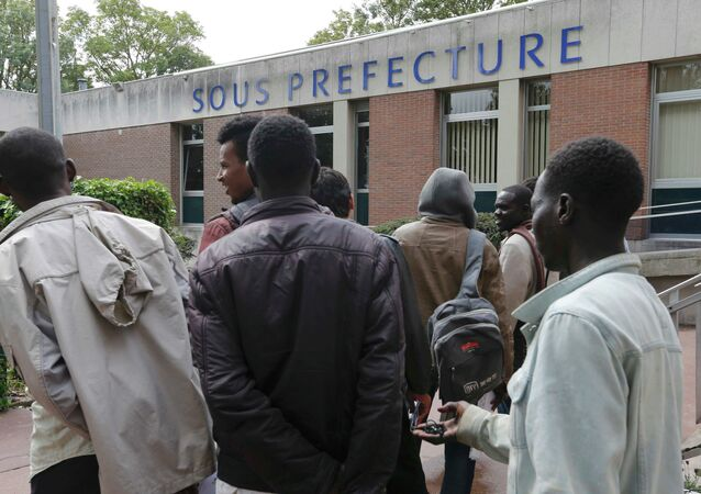 Migrants who seek asylum gather outside the Under Prefecture administration building in Calais, France, August 20, 2015