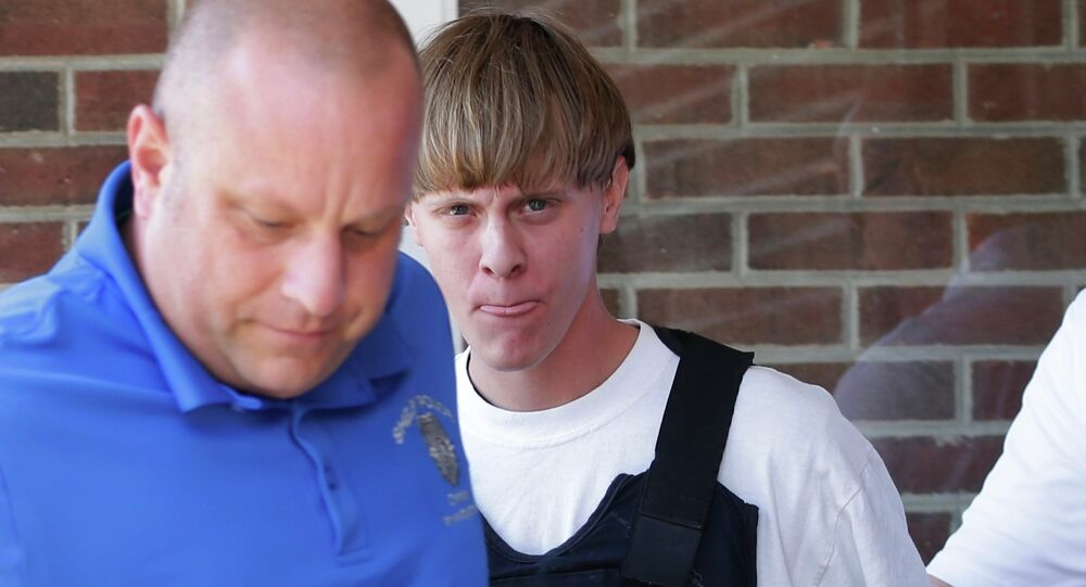 FILE - In this June 18, 2015, file photo, Charleston, S.C., shooting suspect Dylann Storm Roof, center, is escorted from the Sheby Police Department in Shelby, N.C.