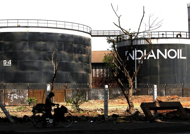 A cyclist walks past an Indian Oil company in Mumbai, India, (File)