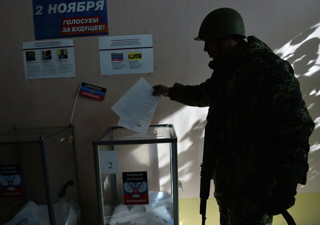 Members of the self-defense forces cast their votes at Polling Station No. 127 during the elections for the leader and the People's Council of the Donetsk People's Republic.