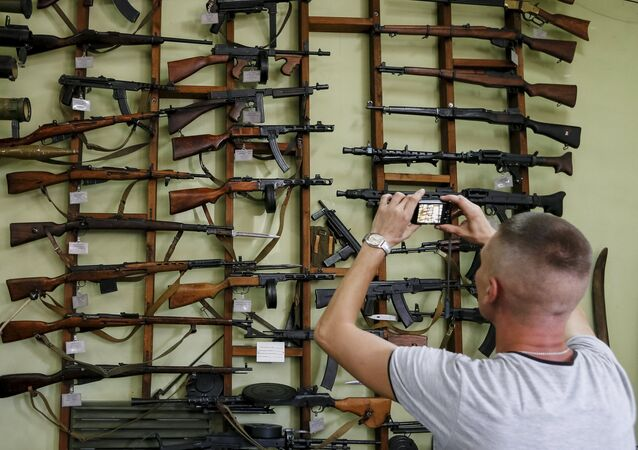 A visitor takes picture of weapons at an exhibition at Phaeton museum in Zaporizhia, Ukraine, August 11, 2015