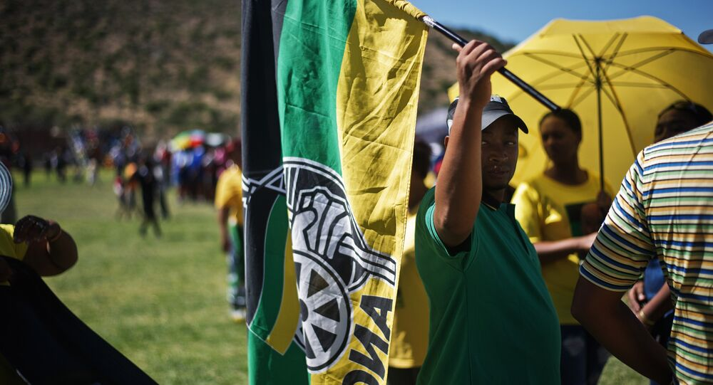 A man holds an African National Congress flag as South African ruling party African National Congress supporters gather to listen to President Jacob Zuma delivering a speech during an Election campaign rally at Umasizakhe stadium in the Eastern Cape city of Graaf-Reinet on April 10, 2014
