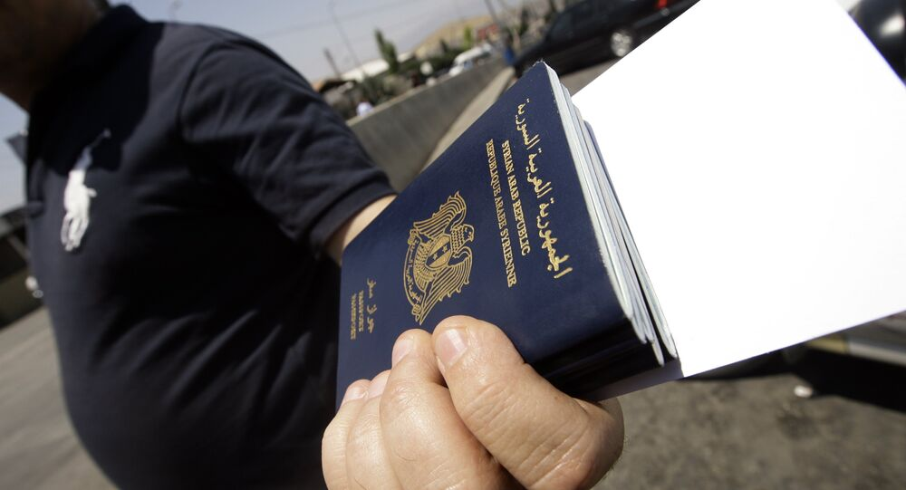 A Syrian man carries passports of relatives before getting them stamped on the Lebanese-Syrian border in al-Masnaa on July 20, 2012