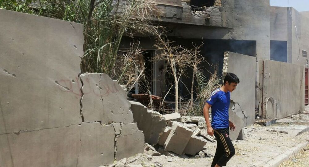 Abdullah Ahmed walks outside his home that was damaged in a bombing in Fallujah, Iraq. The U.S. and its coalition allies have carried out more than 1,000 strikes in Iraq since its campaign began in August - as well as hundreds more by American and Arab air forces in neighboring Syria.