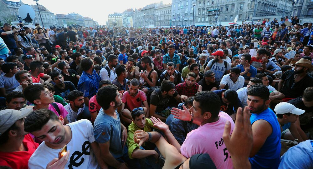 Migrants sit in front of the Keleti (East) railway station in Budapest on September 2, 2015