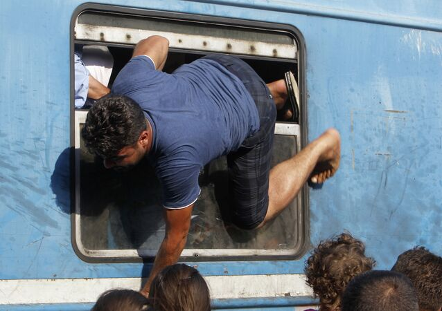 A migrant tries to board a train towards Serbia through a window, at the railway station in the southern Macedonian town of Gevgelija, on Saturday, Aug. 15, 2015
