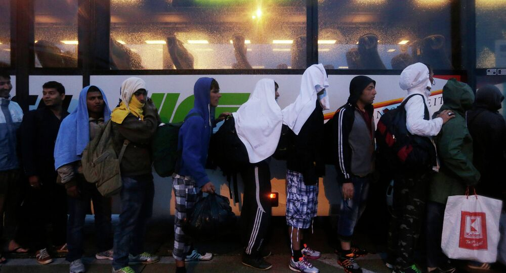 Migrants line up in front of a police bus at the Hungarian-Austrian border in Nickelsdorf, Austria, Saturday, Sept. 5, 2015, where they arrived from Budapest as Austria in the early-morning hours said it and Germany would let them in