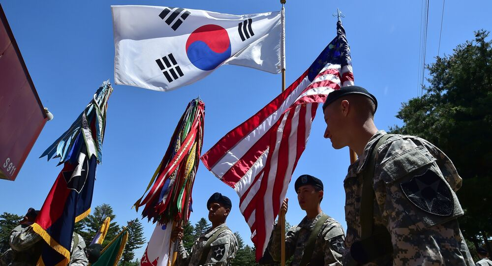 US soldiers hold the flags of South Korea (top) and the US (R) before a South Korea-US Combined Division activation ceremony at a US Army base in Uijeongbu, just north of Seoul, on June 3, 2015