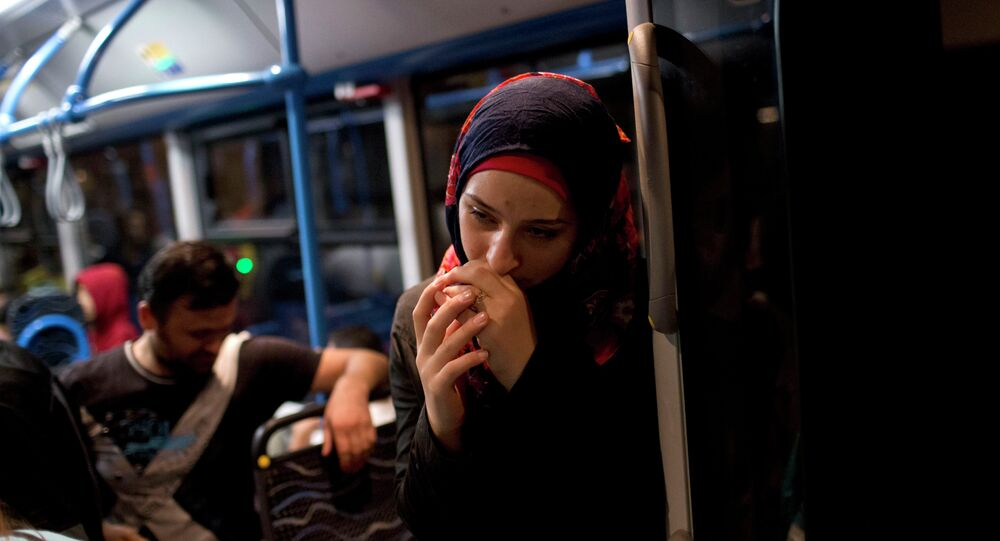 A woman pauses on a bus provided by Hungarian authorities for migrants and refugees at Keleti train station in Budapest, Hungary, Saturday, Sept. 5, 2015