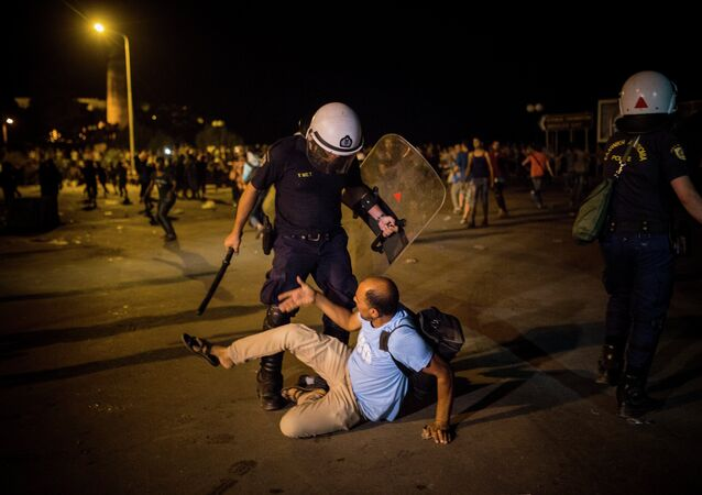 A migrant is confronted by a riot policeman during a protest in which hundreds of migrants and refugees demanded the authorities to let them go to Athens and continue their trip towards Northern Europe, at the port of Mytilene, on the northeastern Greek island of Lesbos, on Saturday, Sept. 5, 2015