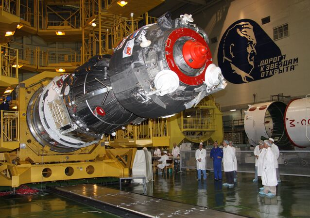 Specialists of RSC Energia work to install the payload shroud on a manned Soyuz TMA-02M spacecraft in the assembly and test complex at Baikonur Cosmodrome, where work proceeds on building a Soyuz-FG space rocket