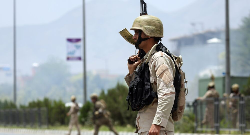 Afghan security forces gather at the site of an attack by Taliban fighters outside the parliament in Kabul, Afghanistan, Monday, June 22, 2015