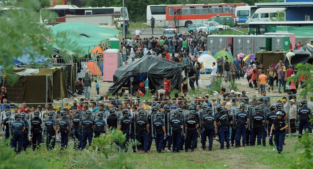 Police officers guard a local refugee camp in the village of Roszke at the Serbian-Hungarian border on September 4, 2015 where migrants are being held